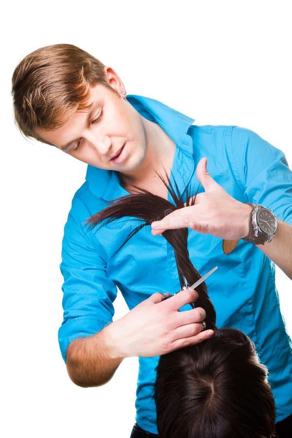 Parrucchiere dell'uomo che lavora con le forbici fotografia stock