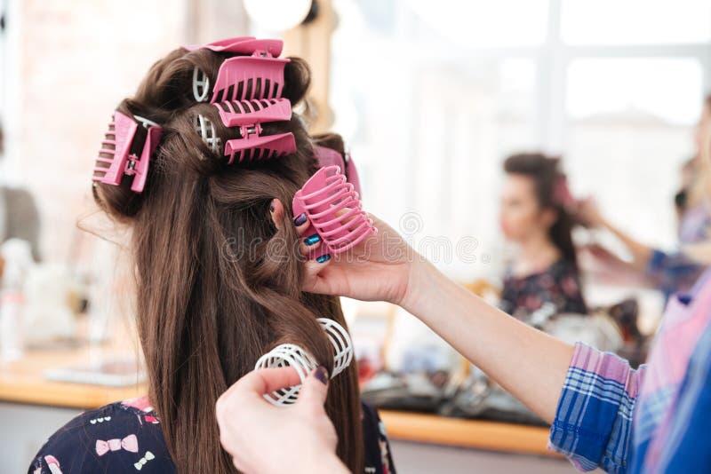 Parrucchiere della donna che decolla i bigodini da capelli lunghi della femmina fotografia stock libera da diritti