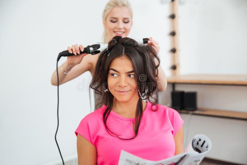 Parrucchiere della donna che fa pettinatura facendo uso del ferro di arricciatura fotografia stock libera da diritti