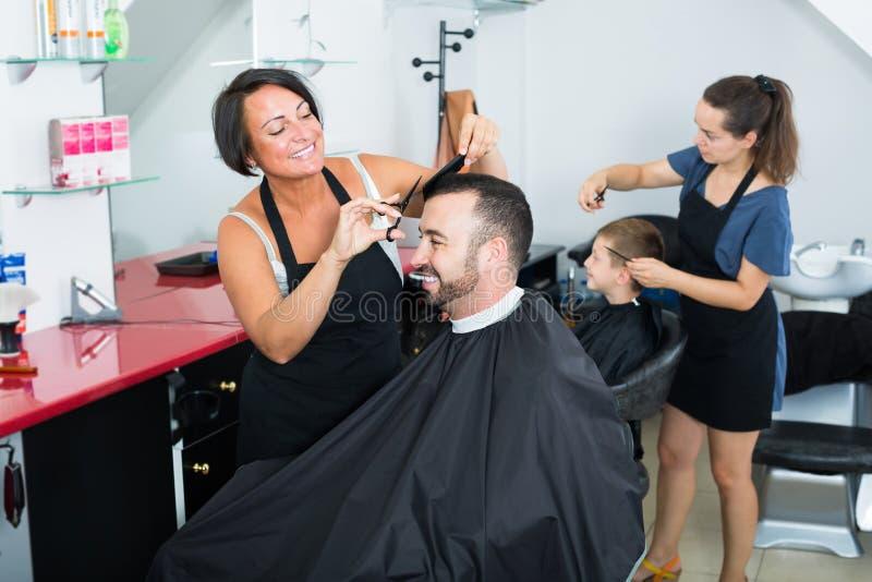Parrucchiere della donna con il maschio sorridente di taglio dello strumento immagini stock
