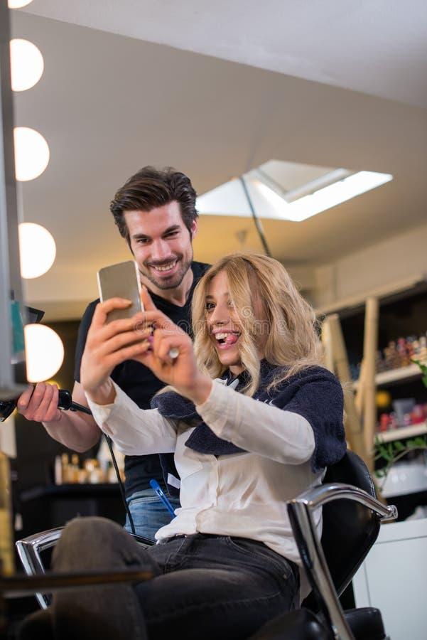 Parrucchiere ed il suo cliente che fanno selfie fotografia stock