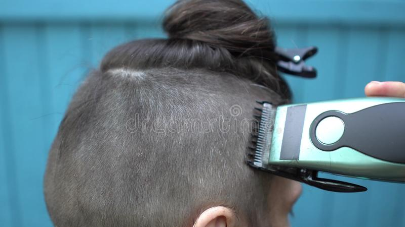 Parrucchiere femminile che fa taglio di capelli maschio con la tosatrice nel salone di lavoro di parrucchiere sulla fine di vista immagini stock libere da diritti