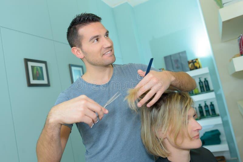 Parrucchiere maschio che fa taglio di capelli per la donna immagine stock