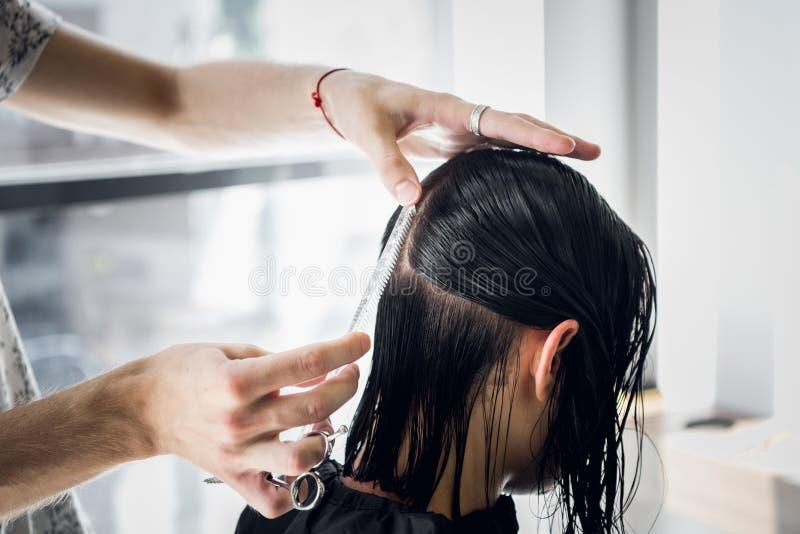 Parrucchiere maschio che sorride e che parla con un cliente mentre facendo un nuovo taglio di capelli con bella giovane donna cas fotografie stock