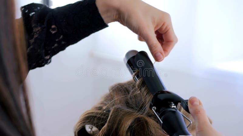 Parrucchiere professionista che fa acconciatura per la donna - fare arriccia fotografia stock libera da diritti