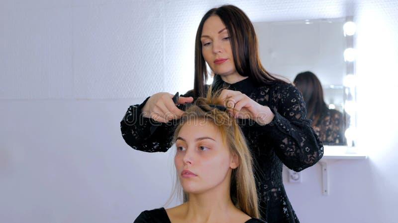 Parrucchiere professionista che fa acconciatura per la giovane donna graziosa fotografia stock libera da diritti