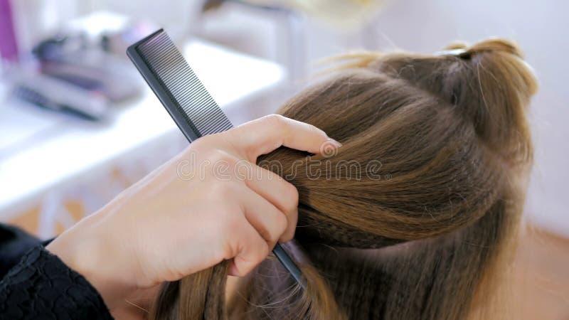 Parrucchiere professionista che fa acconciatura per la giovane donna graziosa fotografie stock libere da diritti