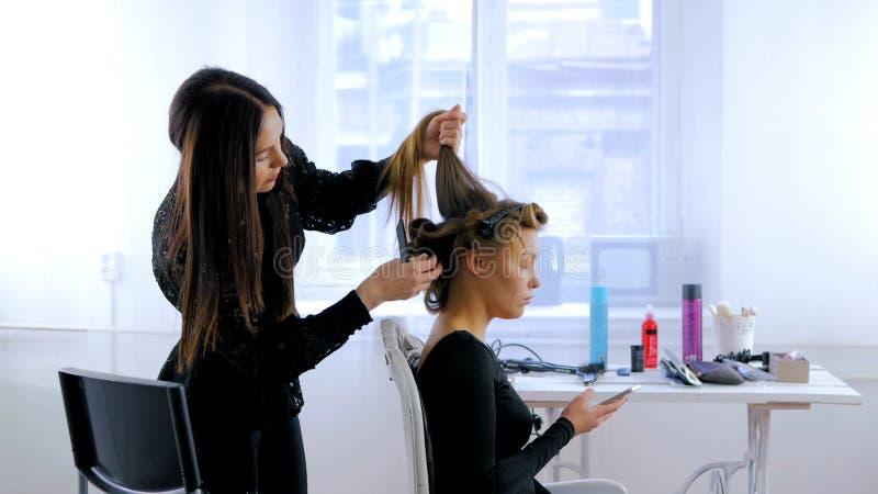 Parrucchiere professionista che fa acconciatura per la giovane donna graziosa con capelli lunghi immagini stock