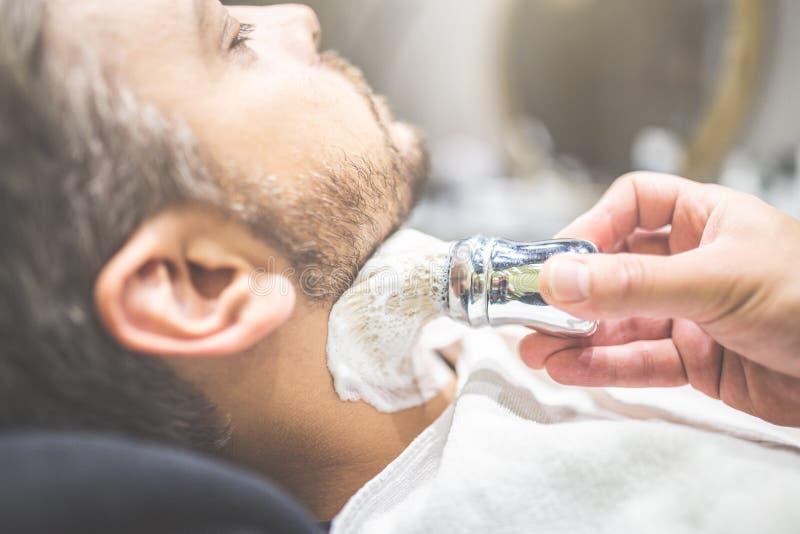 Parrucchiere professionista che si applica radendo schiuma sulla pelle del cliente in parrucchiere fotografia stock libera da diritti