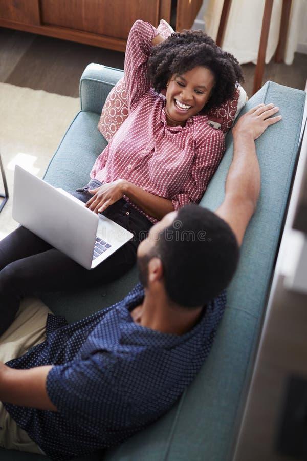 Parsammanträde på Sofa At Home With Woman som använder bärbar datordatoren royaltyfria bilder