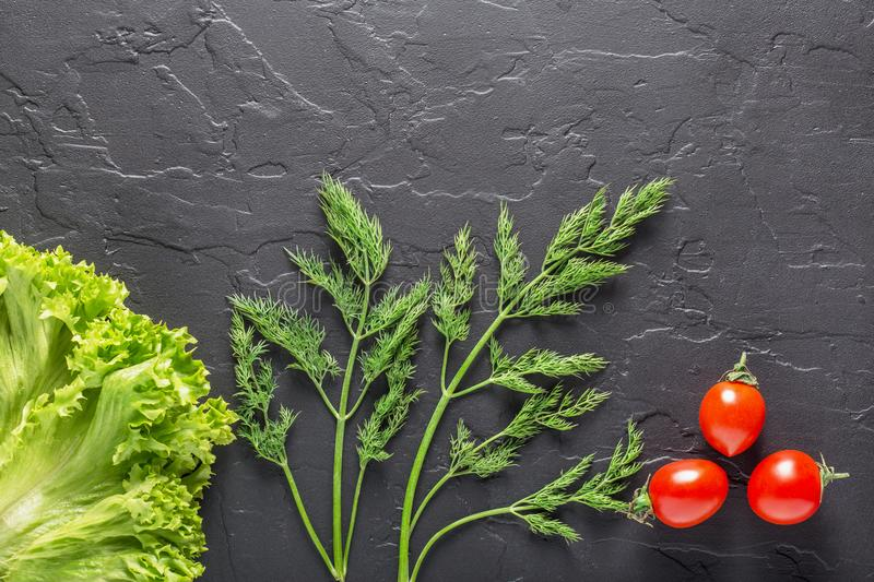 Parsley, dill, cabbage leaves, pepper on a dark concrete background. Fresh products for salads and vegetarian food. Parsley, dill, cabbage leaves, pepper on a royalty free stock image
