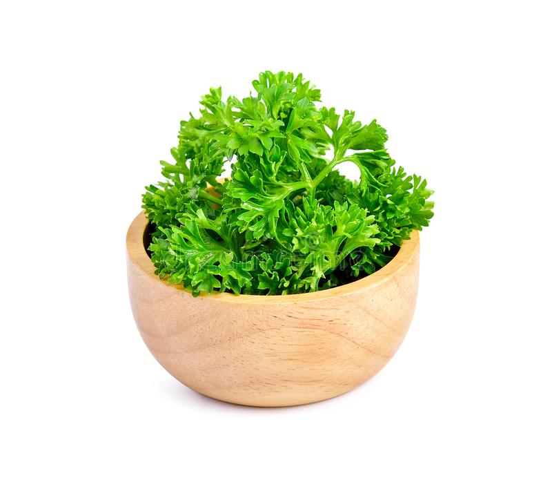 Parsley in wooden bowl isolated on white stock images