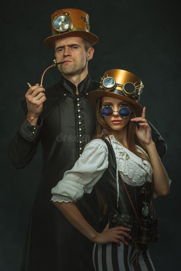 Parsteampunken En man med ett rör och en flicka med exponeringsglas royaltyfria foton
