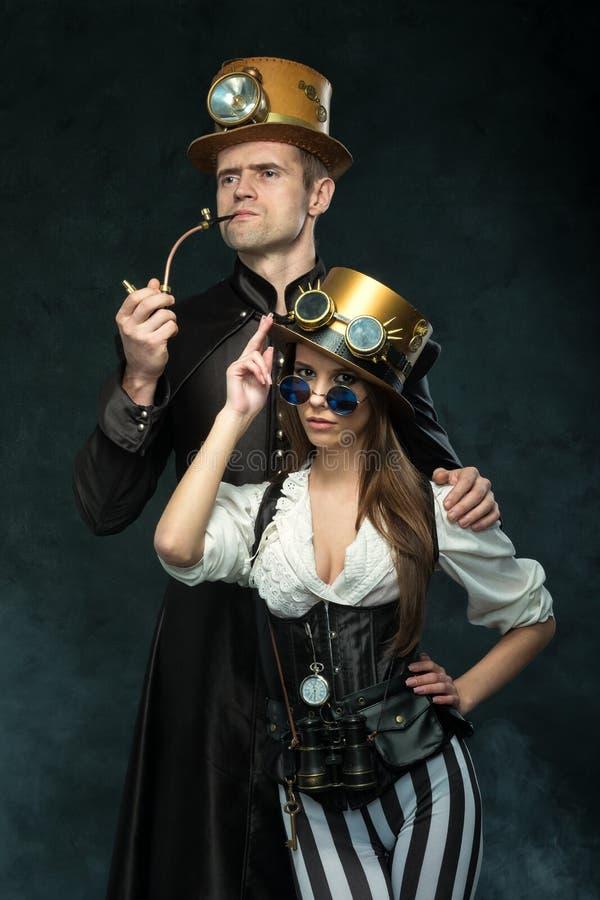 Parsteampunken En man med ett rör och en flicka med exponeringsglas fotografering för bildbyråer