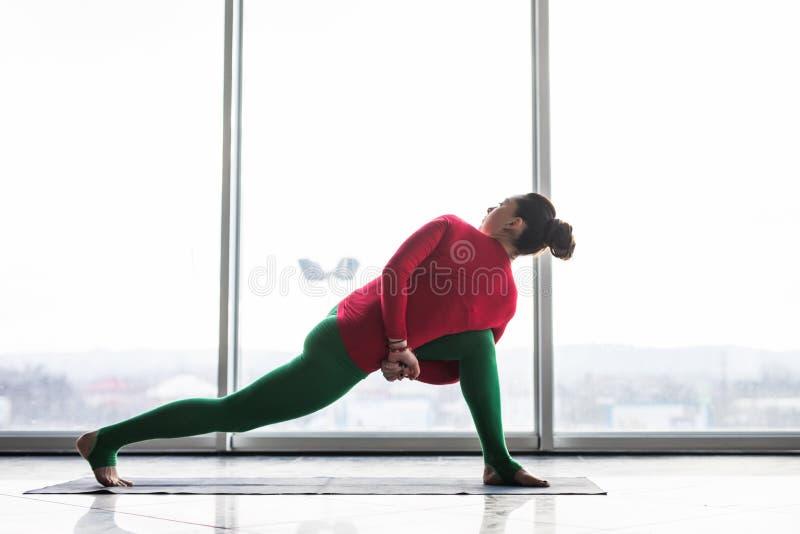 Parsvakonasana de Parivritta A torção bonita da prática da mulher da ioga levanta em um salão grande da janela fotos de stock
