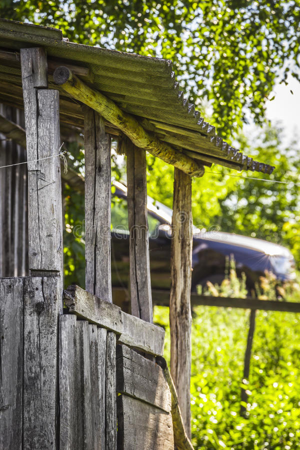 Part of the abandoned wooden hut. Part of the abandoned old wooden hut on the background of a modern car royalty free stock photography