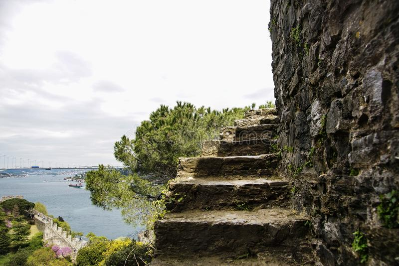 Part of an abrupt ladder of fortress of Rumeli Hisari aspiring into sky. At a background Bosphorus and Bosphorus Bridge. Istanbul. Turkey stock photo