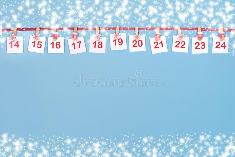 14-24 part of Advent calendar. Sheets with numbers on clips are hanging on red ribbon on blue background royalty free stock photography