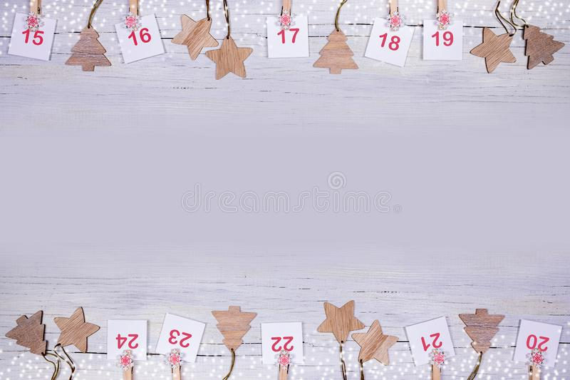 15-24 part of Advent calendar: sheets with numbers and wooden Christmas toys on wooden background toned in lilac royalty free stock photo