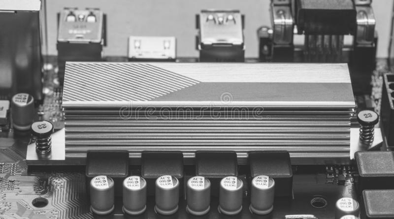 Part of ASUS motherboard with aluminum radiator chipset close-up, black and white photo. Maykop, Russia - November 9, 2018: part of ASUS motherboard with royalty free stock photos