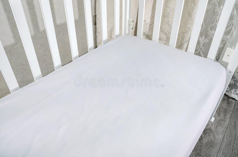 Part of baby cot, close up. Mattress and sheets in white crib. Part of baby cot, close up. Mattress and sheets stock photos