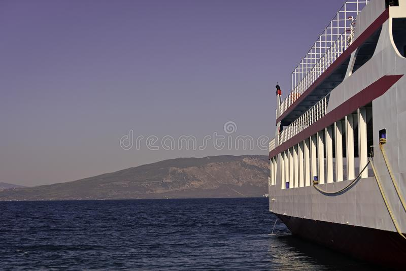 Part of big cruise liner in sea at sunny day. Cruise ship sailing from port. Skyline with mountains and ocean, horizon stock images