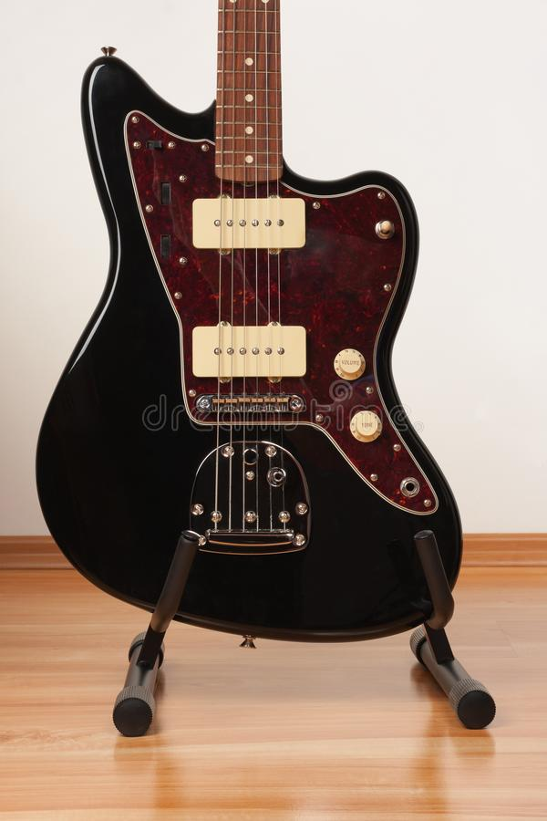 Part of black electric guitar, studio shoot. Red tortoise shell pickguard, alder body, maple neck, two single coil.  stock photography