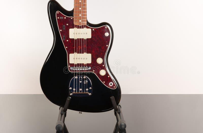 Part of black electric guitar, studio shoot. Red tortoise shell pickguard, alder body, maple neck, two single coil.  stock photo