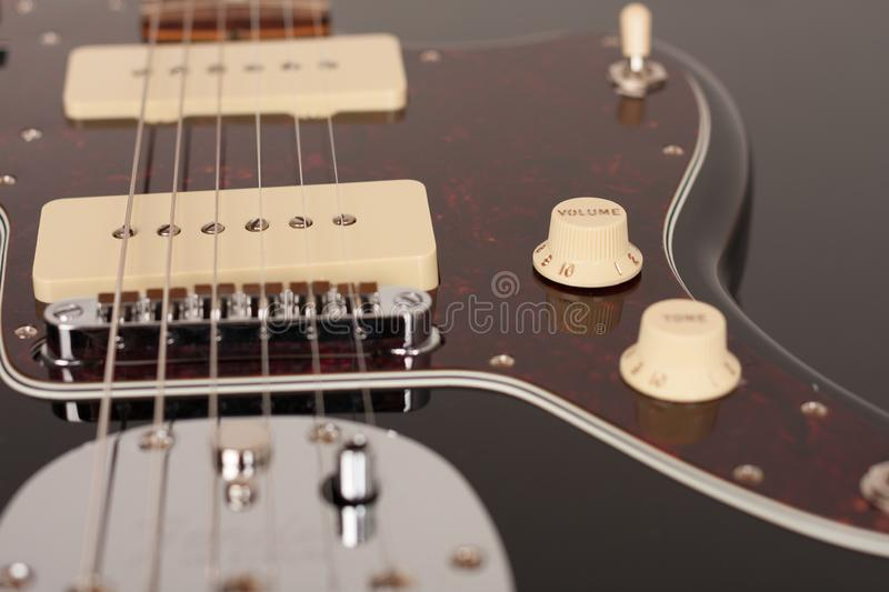 Part of black electric guitar, studio shoot. Red tortoise shell pickguard, alder body, two single coil. Close up of control volume on black electric guitar royalty free stock photo