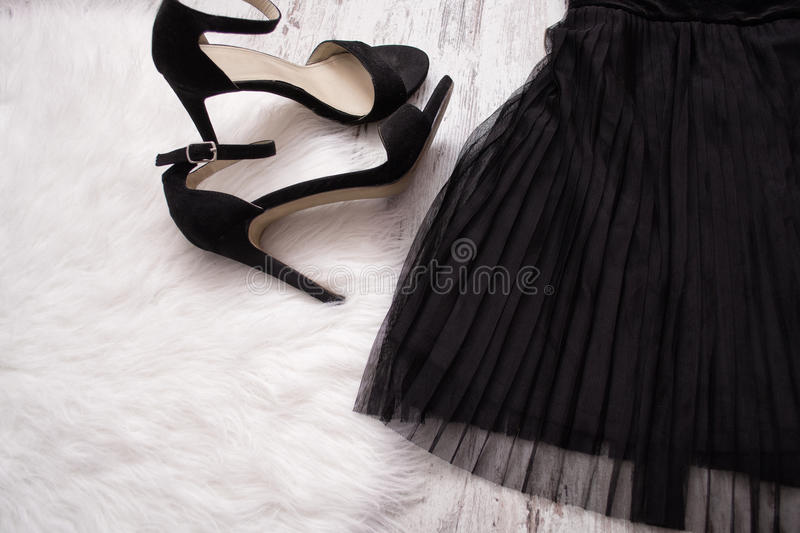 Part of a black pleated skirt and black shoes. Fashion concept. Close-up royalty free stock image