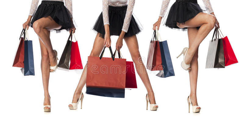 Part body, beautiful female slender legs. girl holding a pa. Per shopping bags, isolated on white background stock image