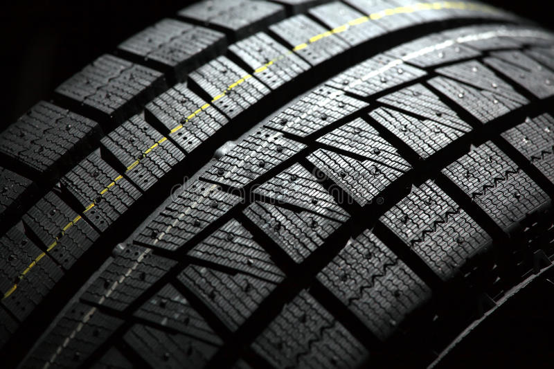 Part of brand new car tyre. Shallow DOF. Black back background stock photos