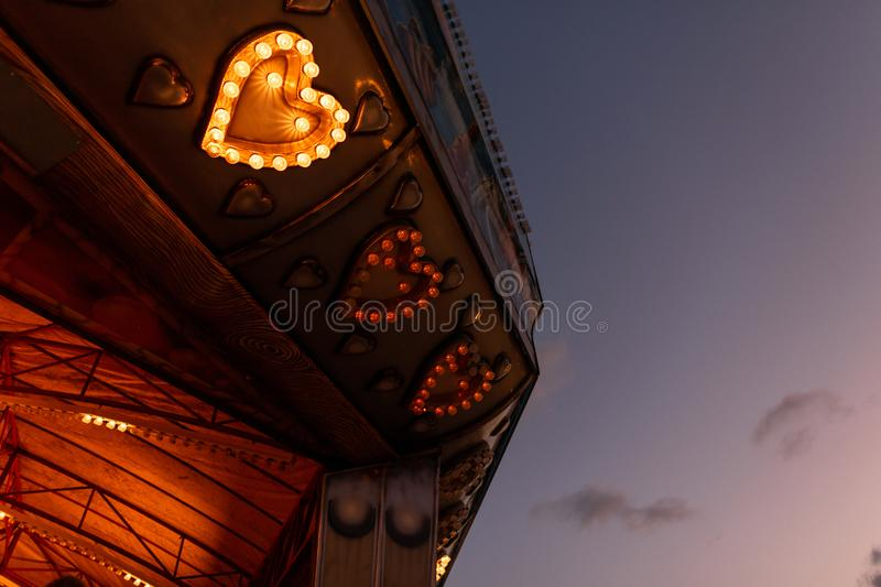Part of a bright vintage carousel with hearts made of light bulbs glows with evening lights.  stock photography