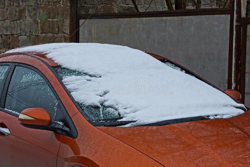 Part of a brown car with snow and frost on the windshield stock photos