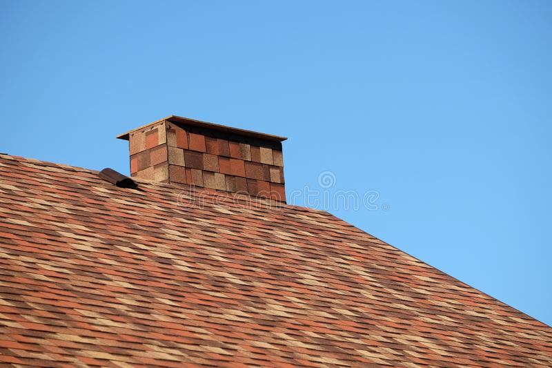 Brown roof of a house covered with soft shingles with short big smokestack close up under cloudless blue sky. Part of brown roof of a house covered with motley royalty free stock photo