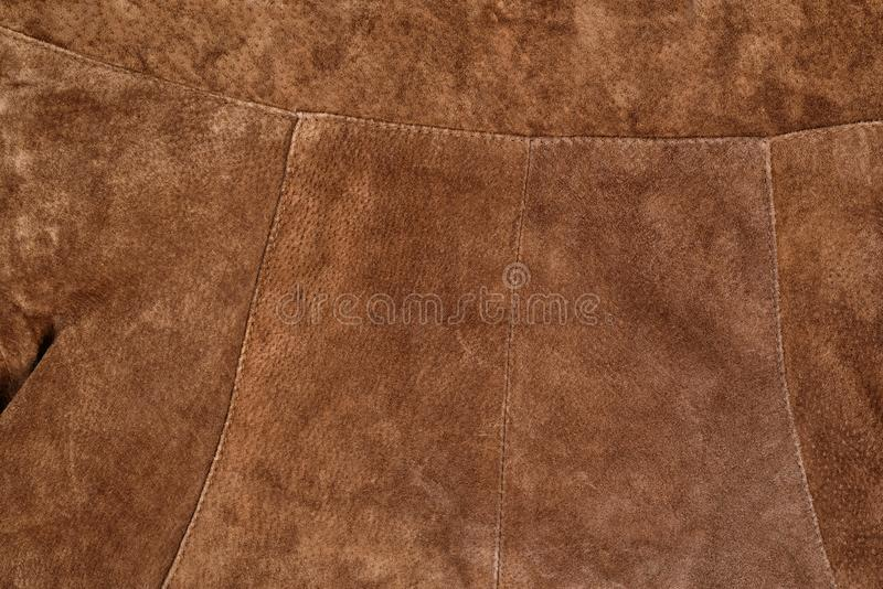 Part of brown textured suede clothing. Genuine leather royalty free stock photos
