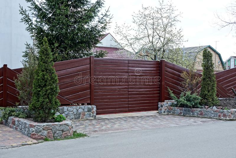 Part of a brown wooden fence and closed gates with decorative coniferous trees on the street. Near the road royalty free stock image
