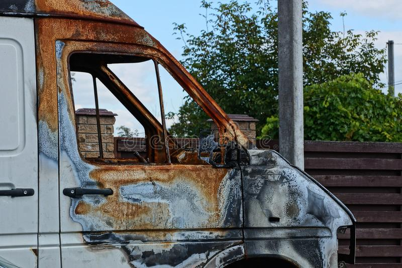 Part of the cab of a burnt white car in the street stock image