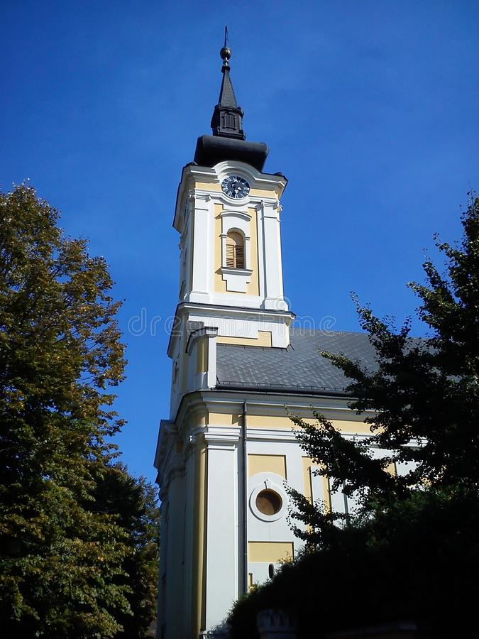 Part of the church building with a dome and a clock under it. The temple is painted in white - yellow colors, the dome and spire. Black. Early autumn with royalty free stock images