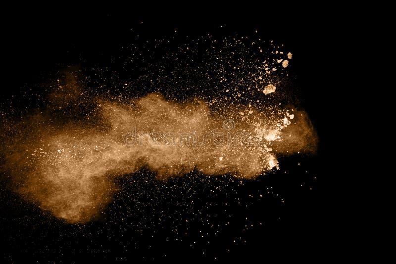 Part?culas de Brown salpicadas en fondo negro El salpicar del polvo de Brown fotografía de archivo libre de regalías