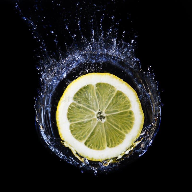 Part de citron tombant dans l'eau. photos stock