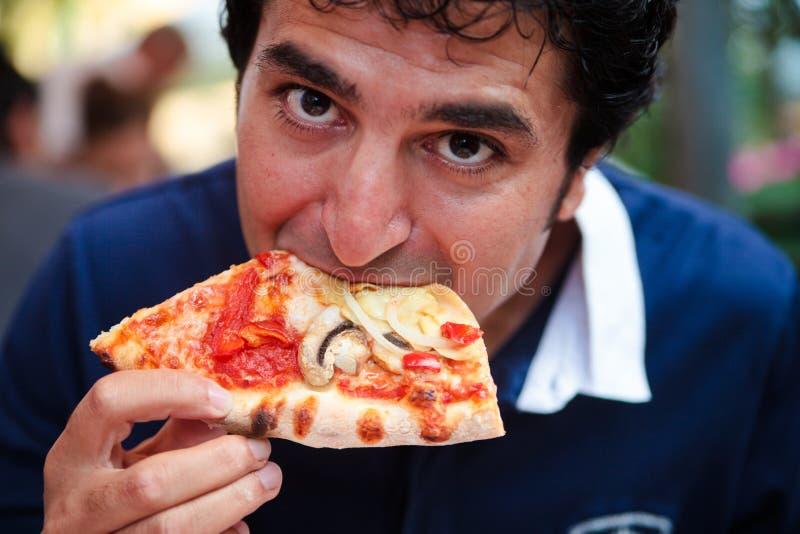 Part de pizza mangeuse d'hommes affamée image stock