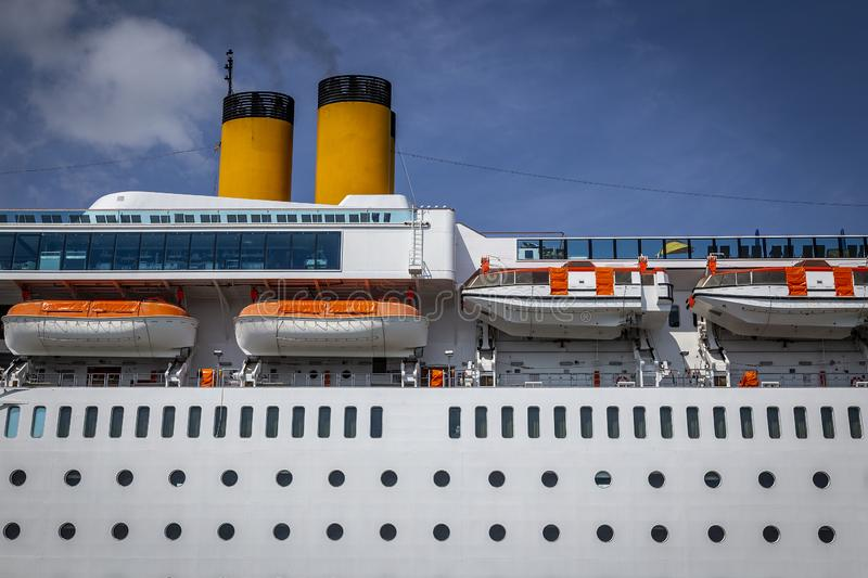 Part of the deck of a large cruise ship. Smoke coming out of the chimneys of a huge passenger ship and rescue boats hung on board stock photos