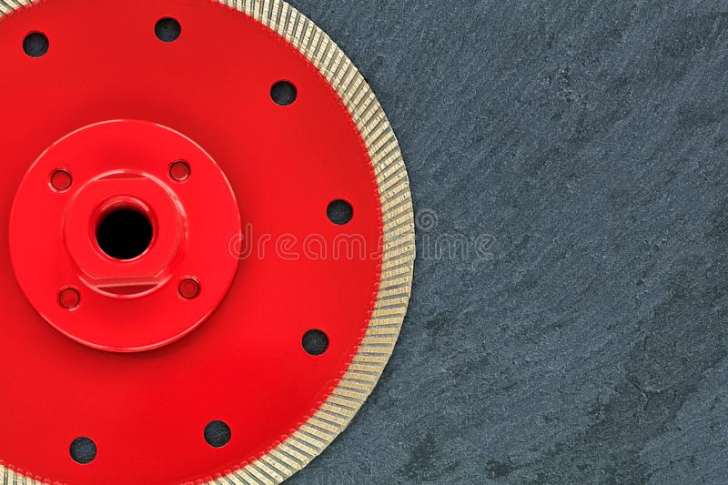 A part of a diamond cutting wheel is red with a threaded nut on a background of gray granite. A part of the diamond cutting wheel is red with a threaded nut, on stock photo