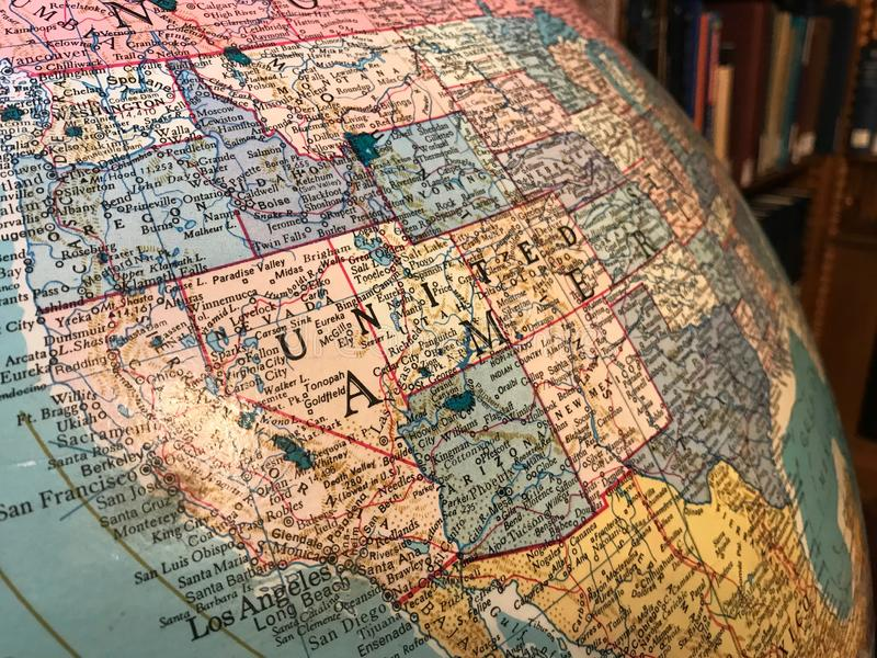 Part of the Earth globe with a political map on the background of books. USA stock photo