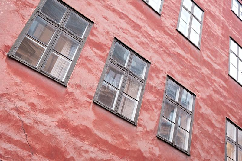 Part of the facade of a red historic building illuminated, reflecting off window panes, in the Old Town Gamla Stan of Stockholm, S stock images