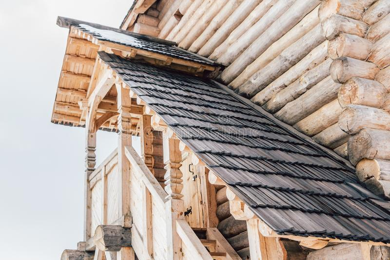 Part of the facade of a wooden house in ancient style. Beautiful wooden veranda on the second floor view from below and sun rays royalty free stock image