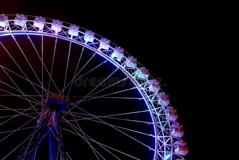 Part of ferris wheel with blue lighting at night royalty free stock photos