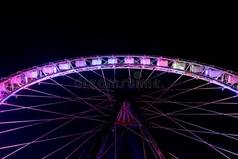 Part of ferris wheel in funfair at night stock image