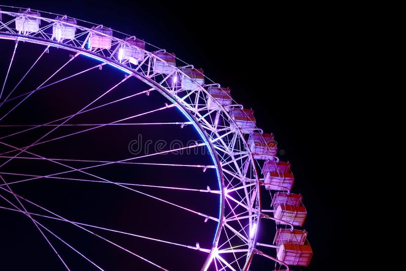 Part of ferris wheel with purple lighting at night royalty free stock photos